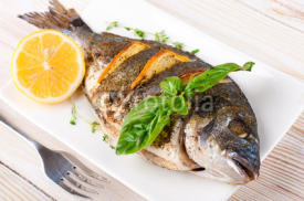 Fototapety Dorado fish with lemon and spices on a wooden board