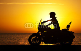 Naklejki Woman biker over sunset