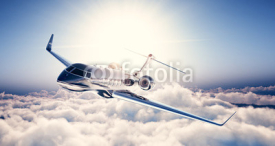 Obrazy i plakaty Photo of black luxury generic design private jet flying in blue sky. Huge white clouds and sun at background. Business travel concept. Horizontal. 3d rendering