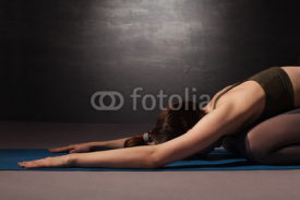 Naklejki Mature woman practicing yoga on the floor