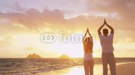 Fototapety Yoga, fitness, sport, and wellness lifestyle concept. Couple doing yoga exercises on beach from back at sunrise on serene peaceful beach. Relaxation and yoga meditation on Lanikai, Oahu, Hawaii