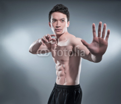 Fototapety Muscled asian kung fu man in action pose. Blood stripes on his c
