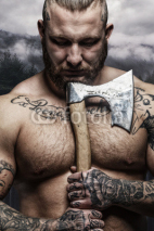 Naklejki Portrait of tattooed male with vikings axe.