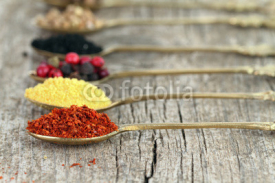 Fototapety Old spoons with spices on wooden background