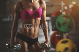 Obrazy i plakaty Brutal athletic woman pumping up muscles with dumbbells