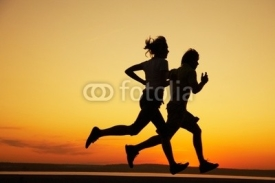Obrazy i plakaty Young couple run together on a sunset