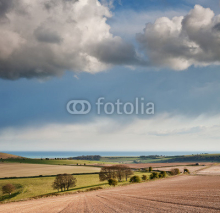 Fototapety Stunning landscape with stormy sky over rural hills