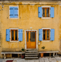 Fototapety Front of an old house with blue shutters and yellow wall