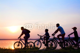 Fototapety family on bicycles admiring the sunset on the lake. silhouette