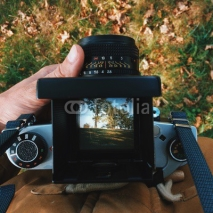 Obrazy i plakaty man photographer is making  landscape photography with old film camera