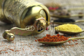 Fototapety Old spoons with spices and pepper grinder on wooden background