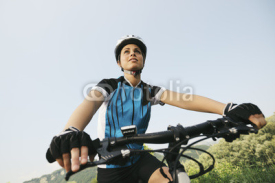 Fototapety young woman training on mountain bike and cycling in park