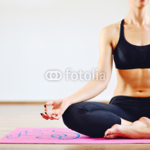Fototapety Young woman doing yoga indoors - body part