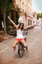 Fototapety Happy young woman riding on bicycle with her boyfriend