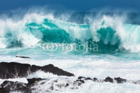Fototapety Turquoise rolling wave slaming on the rocks