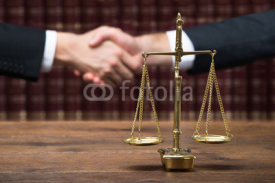 Fototapety Justice Scale On Table With Judge And Client Shaking Hands