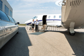 Naklejki Stewardess And Pilot Standing Neat Limousine And Private Jet