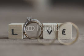 Obrazy i plakaty Wedding and engagement rings with inscription love