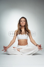 Fototapety Young woman in yoga pose in studio on white background