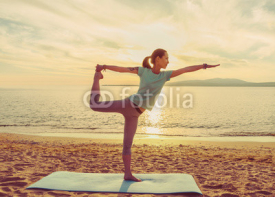 Fototapety Young woman practicing yoga on beach