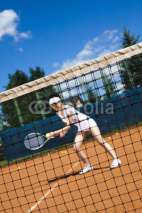 Fototapety Young woman playing tennis