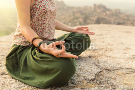 Fototapety Young woman meditating at mountain cliff on sunrise. Hands close-up