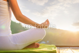 Fototapety Woman doing yoga on the shore - half figure sitting