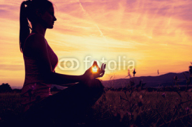 Naklejki Young athletic woman practicing yoga on a meadow at sunset, silhouette