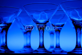Obrazy i plakaty Wineglasses arranged in rows on the table in blue light