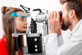 Obrazy i plakaty Eye doctor checking vision of young female patient with ophthalmologic device in the cabinet