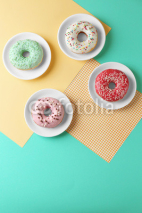 Plates with delicious donut on colorful background