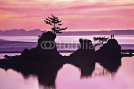 Naklejki Sunset of Beach with rock formations and pink and purple tones of light/Sunset of pink and purple colors on beach in Siletz Bay, Oregon with silhouettes of rock and hiker
