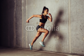 Obrazy i plakaty Slim attractive sportswoman running against a concrete background