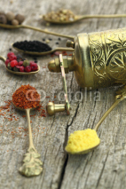 Obrazy i plakaty Old spoons with spices and pepper grinder on wooden background