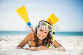 Obrazy i plakaty Smiling woman wearing flippers at the beach
