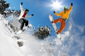 Naklejki Snowboarders jumping against blue sky