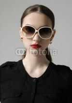 Naklejki Fashion woman portrait wearing sunglasses on gray