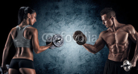 Obrazy i plakaty Athletic man and woman with a dumbells.