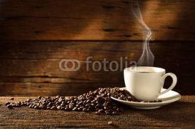 Fototapety Coffee cup and coffee beans on old wooden background