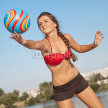 Fototapety Young beautiful lady is playing volleyball on the beach