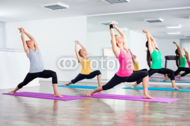 Fototapety Four girls practicing yoga, Virabhadrasana / Warrior pose