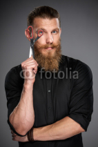 Obrazy i plakaty Serious hipster man with beard and mustashes holding scissors looking through it, over grey background