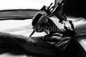 Naklejki Tattooist makes tattoo on clients arm in bw