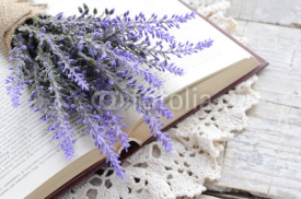Fototapety Bunch of lavender laying upon open book on vintage doily