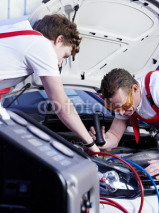 Naklejki Two motor mechanic checking the air handling unit of a car
