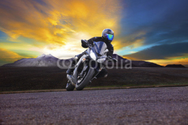 Naklejki young man riding motorcycle in asphalt road curve with rural and