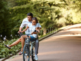 Fototapety Happy couple cycling in the summer park