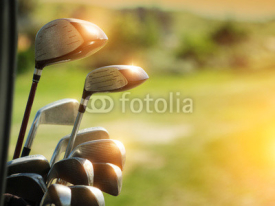 Fototapety Golf clubs drivers over green field background