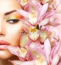 Naklejki Beautiful Girl With Orchid Flowers. Beauty Model Woman Face