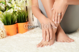 Naklejki Female hands and feet with manicure and a pedicure